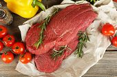 Raw beef steak on paper with vegetables and greens on wooden background