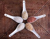 Different types of rice in spoons on wicker background