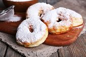 Delicious donuts with icing and powdered sugar on wooden background