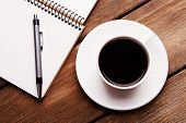 Cup of coffee on saucer with notebook and pen on wooden table background