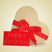 a heart-shaped gift and a red signboard with the text happy birthday written in it on a beige background, with a retro effect