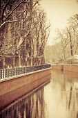 Park With River And Embankment Covered With Snow