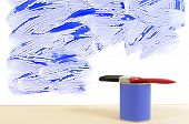 stock photo of untidiness  - Partly finished untidy or messy blue painted wall with paint can and paintbrush - JPG