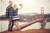 image of golden gate bridge  - couple in taking selfie in front of golden gate bridge - JPG