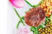fresh grilled meat medalion on green beans with vegetables
