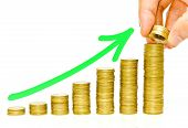 picture of golden coin  - hand putting golden coins to piles of coins arranged as a graph with green arrow - JPG