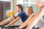Thirsty man drinking orange juice in gym on spinning bike