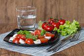 image of black-cherry  - Italian Caprese salad with cherry tomatoes and baby mozzarella on black plate - JPG