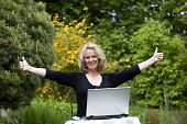 woman with laptop posing thumbs up