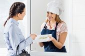 Young woman buying uncooked ravioli pasta packet from female chef through window