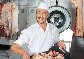 pic of slaughterhouse  - Portrait of happy male butcher carrying meat pieces in crate at butchery - JPG