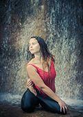 Woman practicing yoga near waterfall. Twisted lotusl Pose. Bharadvajasana