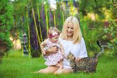 Young mother with child and a cat having fun on green lawn on summer day