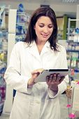 Pharmacist Working With Tablet In Pharmacy