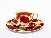 full red cup of tea with two saucers, isolated on white background