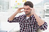 Businessman sitting with severe headache in the office