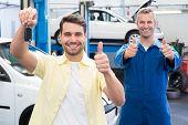 Customer and mechanic smiling at camera at the repair garage