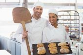 Team of bakers smiling at camera with trays of loaves in the kitchen of the bakery
