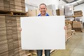 Smiling warehouse worker holding large white poster in a large warehouse