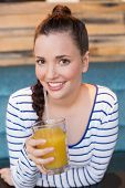 Young woman having glass of orange juice at the cafe