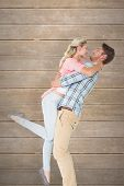 Handsome man picking up and hugging his girlfriend against wooden planks