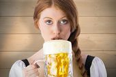 Oktoberfest girl drinking jug of beer against bleached wooden planks background