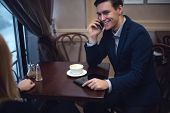 Handsome entrepreneur enjoying his launch in a cafe talking with someone by the phone.