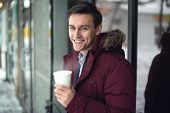 Young businessman in a suit and winter coat is drinking hot coffee at cold street with steam bright