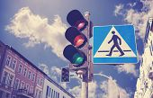 Retro Filtered Photo Of Traffic Lights And Pedestrian Crossing Sign In A City.