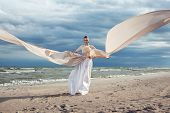 stock photo of incredible  - Incredible portrait of model with extremely long dress at the beach - JPG