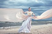Fashionable Model Holding A Flying Long Dress. Exclusive Dress. Blue Sky Background