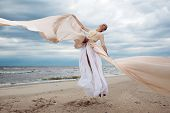 Model Jumps With Long Dress Like A Wings At The Beach