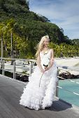 The beautiful woman in a long dress of the bride on the wooden bridge on the tropical island