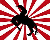 stock photo of bucking bronco  - Silhouette of a rodeo cowboy with a red and white background - JPG