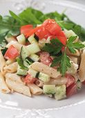 Italian pasta salad with tomato, cucumber and parsley
