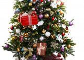 Decorated Christmas tree on floor on light wall background