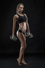 foto of tanga  - Nice sexy woman doing workout with dumbbell isolated over black background - JPG