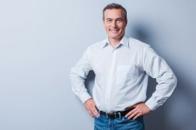 image of mature adult  - Confident mature man in shirt looking at camera and smiling while holding hands on hip and standing against grey background - JPG