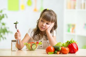 stock photo of disgusting  - Child girl looks with disgust for healthy food - JPG