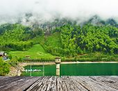 picture of emerald  - Beautiful emerald mountain lake in Switzerland under low clouds - JPG