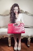 stock photo of bolivar  - Pretty model girl sitting on victorian sofa holding a red exclusive purse and looking into it - JPG