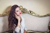 pic of bolivar  - Pretty model girl sitting on victorian sofa posing for camera holding phone to her ear - JPG