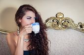 stock photo of mystique  - Pretty model girl wearing blue dress sitting on victorian sofa drinking from coffee cup - JPG
