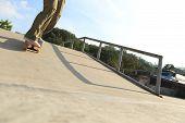 pic of skateboard  - young skateboarder legs skateboarding at skatepark ramp - JPG