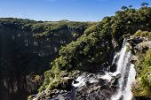 image of ponds  - A waterfall leads to a small pond before falling into emptiness at a canyon surrounded by green trees under a blue sky - JPG