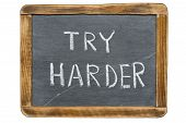 stock photo of slogan  - try harder slogan handwritten on vintage slate chalkboard isolated on white - JPG