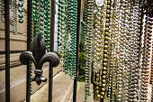 picture of fleur de lis  - Colorful collections of Mardi Gras bead hanging from a rail with a fleur de lis - JPG