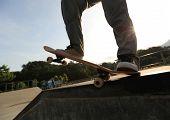 picture of skateboard  - skateboarder legs riding skateboard at sunrise  skatepark - JPG
