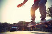 image of skateboard  - skateboarder legs riding skateboard at skatepark ramp - JPG