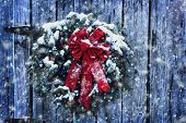 foto of christmas wreath  - Rustic Christmas wreath on old weathered door with Christmas lights in a snow storm - JPG